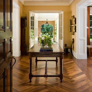 Cette photo montre un hall d'entrée chic avec un mur jaune, un sol en bois brun, une porte double, une porte en verre et un sol marron.