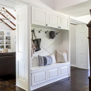 Exempel på ett mellanstort lantligt kapprum, med mellanmörkt trägolv, en enkeldörr, en vit dörr, grå väggar och brunt golv