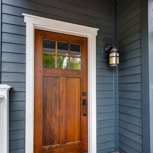 シカゴの中くらいの片開きドアヴィクトリアン調のおしゃれな玄関ドア (グレーの壁、塗装フローリング、茶色いドア、茶色い床、板張り天井、パネル壁) の写真