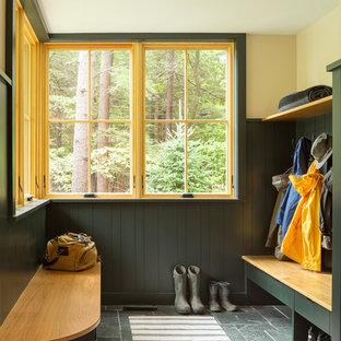 Cette image montre une entrée chalet avec un vestiaire, un mur jaune et un sol gris.