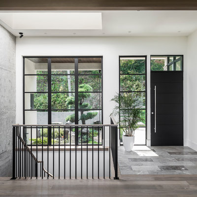Entryway - large contemporary gray floor entryway idea in Vancouver with white walls and a black front door