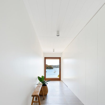 Inspiration for a contemporary gray floor entryway remodel in Sydney with white walls and a glass front door