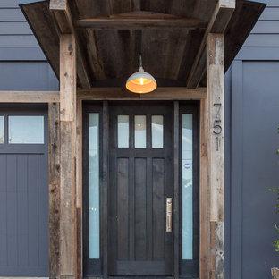 Imagen de puerta principal urbana, grande, con paredes azules, suelo de cemento, puerta simple y puerta de madera oscura