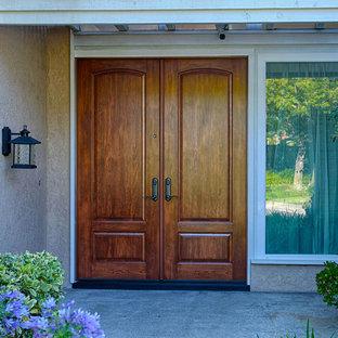 Idée de décoration pour une très grand porte d'entrée tradition avec un mur marron, une porte double et une porte en bois brun.