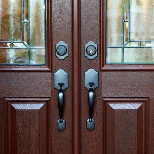 Idee per una grande porta d'ingresso classica con pareti arancioni, una porta a due ante e una porta in legno bruno