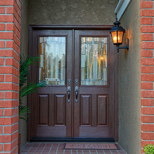 Entryway - large traditional entryway idea in Orange County with orange walls and a medium wood front door