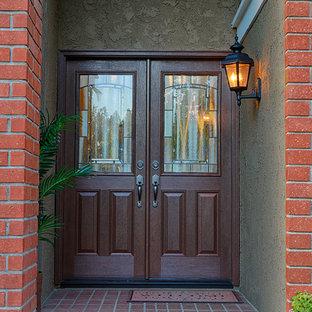 Foto de puerta principal clásica, grande, con parades naranjas, puerta doble y puerta de madera en tonos medios