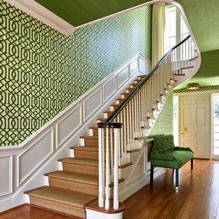 ローリーの広い片開きドアエクレクティックスタイルのおしゃれな玄関ホール (緑の壁、無垢フローリング、白いドア) の写真