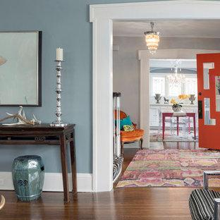 ミネアポリスの片開きドアエクレクティックスタイルのおしゃれな玄関ドア (グレーの壁、無垢フローリング、オレンジのドア、茶色い床) の写真