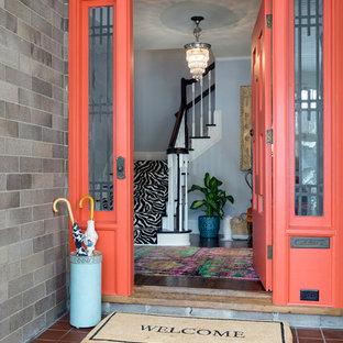 ミネアポリスの片開きドアエクレクティックスタイルのおしゃれな玄関ドア (グレーの壁、オレンジのドア) の写真