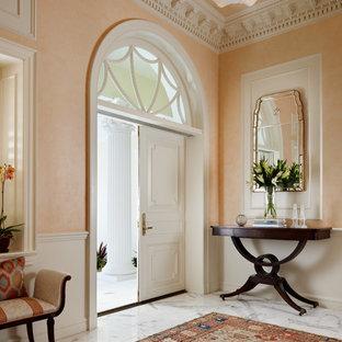 Стильный дизайн: большое фойе в классическом стиле с оранжевыми стенами, мраморным полом, двустворчатой входной дверью, белой входной дверью и серым полом - последний тренд