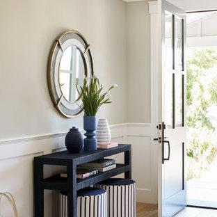Idee per un corridoio chic di medie dimensioni con pareti beige, parquet chiaro, una porta singola, pavimento beige e boiserie