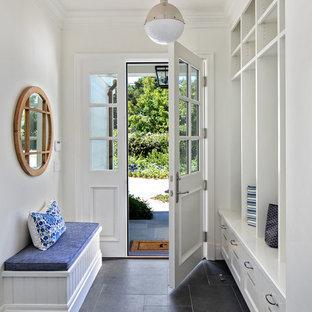 Идея дизайна: тамбур в классическом стиле с белыми стенами, одностворчатой входной дверью, белой входной дверью и черным полом