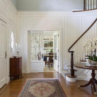 Imagen de distribuidor panelado, clásico, panelado, con paredes blancas, suelo de madera en tonos medios, puerta simple, puerta blanca, suelo marrón y panelado