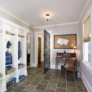 Cette photo montre une entrée chic avec un vestiaire, un mur gris, un sol en ardoise, une porte simple, une porte en verre et un sol multicolore.