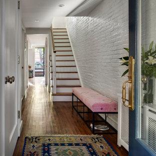 Стильный дизайн: фойе в классическом стиле с темным паркетным полом, одностворчатой входной дверью, синей входной дверью и кирпичными стенами - последний тренд