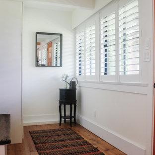 Mittelgroßer Landhausstil Eingang mit Foyer, weißer Wandfarbe, braunem Holzboden, Einzeltür, orangefarbener Tür, braunem Boden, freigelegten Dachbalken und Holzwänden