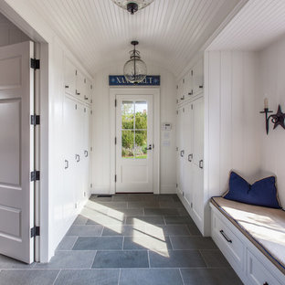 Photo of a large beach style mudroom in Boston with white walls, a single front door, a glass front door and grey floor.