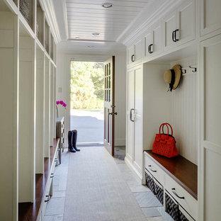 Exemple d'une très grand entrée chic avec un vestiaire, un mur blanc, un sol en ardoise, une porte simple et une porte marron.