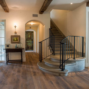 Example of a large tuscan medium tone wood floor entryway design in Other with beige walls and a white front door