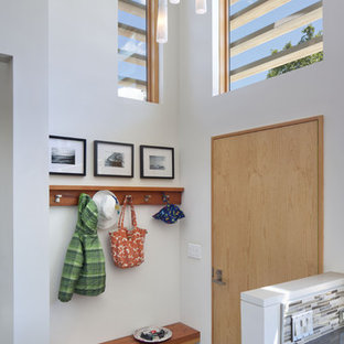 Entryway - contemporary porcelain floor entryway idea in San Francisco with white walls and a light wood front door