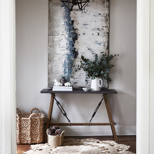 Inspiration for a transitional entry hall in Melbourne with grey walls, dark hardwood floors and brown floor.