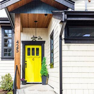 Ispirazione per un ingresso o corridoio country di medie dimensioni con una porta singola, una porta gialla, pareti beige, pavimento in cemento e pavimento grigio