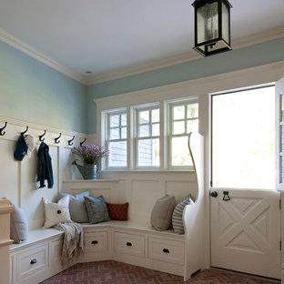 Lantlig inredning av ett mellanstort kapprum, med blå väggar, tegelgolv, en tvådelad stalldörr och en vit dörr