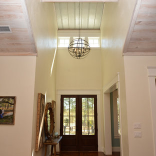 Large country medium tone wood floor entryway photo in Atlanta with yellow walls and a glass front door