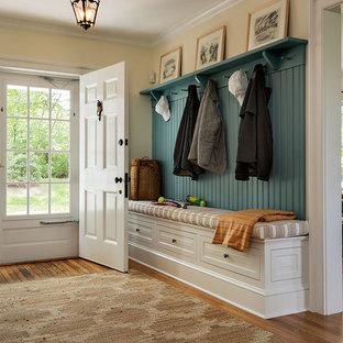 Idée de décoration pour un hall d'entrée tradition avec un sol en bois brun, une porte simple, une porte blanche et un mur jaune.