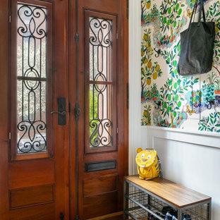 Modelo de vestíbulo clásico renovado con paredes blancas, puerta doble, puerta de madera en tonos medios y suelo amarillo