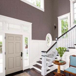 Inspiration for a large transitional dark wood floor entryway remodel in Charlotte with brown walls and a gray front door
