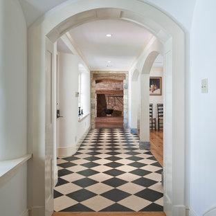 Cette image montre un hall d'entrée rustique avec un mur blanc, une porte simple et un sol multicolore.