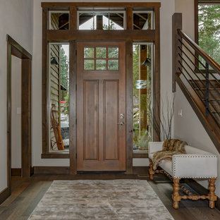 Example of a mountain style dark wood floor and brown floor entryway design in Seattle with white walls and a dark wood front door