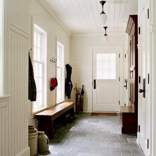 Inredning av ett klassiskt mellanstort kapprum, med skiffergolv, vita väggar, en enkeldörr, en vit dörr och svart golv