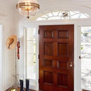Exempel på en klassisk foajé, med vita väggar, mörkt trägolv, en enkeldörr, mörk trädörr och brunt golv