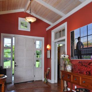 ハワイの中くらいの片開きドアコンテンポラリースタイルのおしゃれな玄関ロビー (ピンクの壁、コンクリートの床、白いドア、茶色い床) の写真