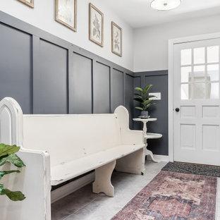 Idee per un grande corridoio con pareti bianche, una porta singola, una porta bianca, pavimento grigio e boiserie
