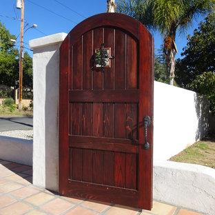 На фото: входная дверь среднего размера в средиземноморском стиле с белыми стенами, полом из терракотовой плитки, одностворчатой входной дверью и входной дверью из темного дерева