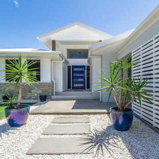 Modelo de puerta principal costera con paredes blancas, suelo de cemento, puerta simple y puerta azul