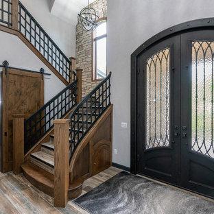 На фото: большое фойе в средиземноморском стиле с серыми стенами, светлым паркетным полом, двустворчатой входной дверью, черной входной дверью и бежевым полом с