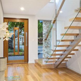 Imagen de distribuidor marinero con paredes blancas, suelo de madera en tonos medios, puerta simple, puerta de madera en tonos medios y suelo beige