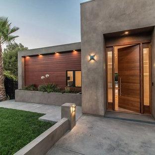 На фото: входные двери в современном стиле с серыми стенами, бетонным полом, одностворчатой входной дверью, входной дверью из дерева среднего тона и серым полом