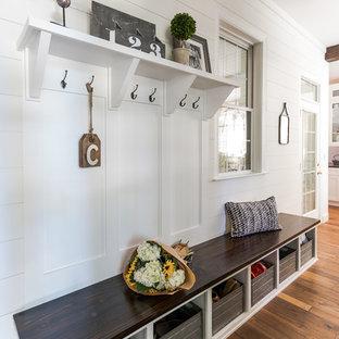 Modelo de vestíbulo posterior campestre con paredes blancas, suelo de madera en tonos medios y suelo marrón