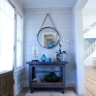 Foto de hall costero, de tamaño medio, con suelo de madera clara, puerta simple, paredes grises, puerta de madera clara y suelo beige