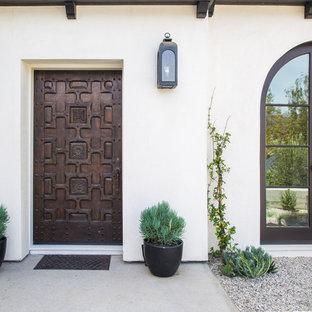 Idée de décoration pour une porte d'entrée méditerranéenne avec un mur blanc, béton au sol, une porte simple et une porte en bois foncé.