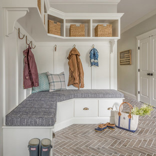 Example of a cottage brick floor and red floor mudroom design in Boston with gray walls