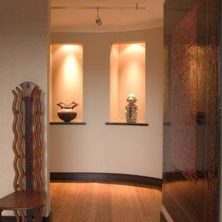 Cette image montre une entrée design avec un couloir, un mur beige, un sol en bambou et une porte pivot.