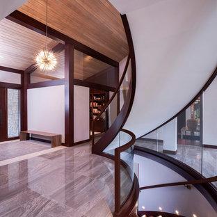 デトロイトの広い片開きドアコンテンポラリースタイルのおしゃれな玄関ロビー (グレーの壁、磁器タイルの床、濃色木目調のドア、グレーの床) の写真