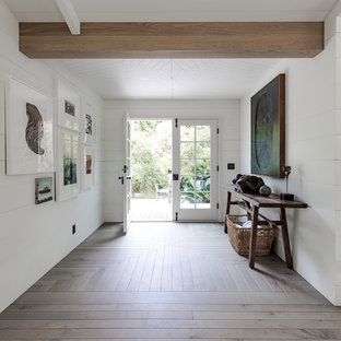 Mid-sized coastal medium tone wood floor and brown floor entryway photo in Santa Barbara with white walls and a white front door